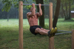 fit guy doing bar pull ups in the park