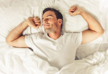 man stretching waking up from good night sleep