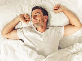 man stretching waking up from good night sleep