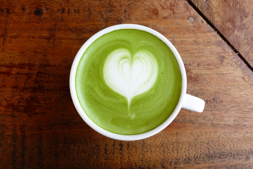 cup of green coffee latte with heart foam