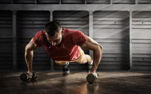 fit guy doing dumbbell push ups