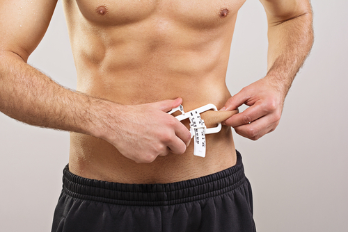 fit guy measuring body fat from belly with caliper
