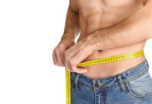 fit guy measuring waist circumference