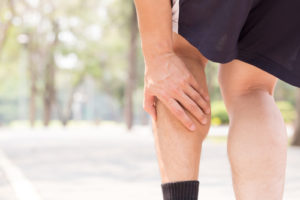 man suffering from leg cramps while running
