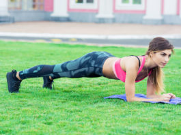 fit woman planking in the field tabata