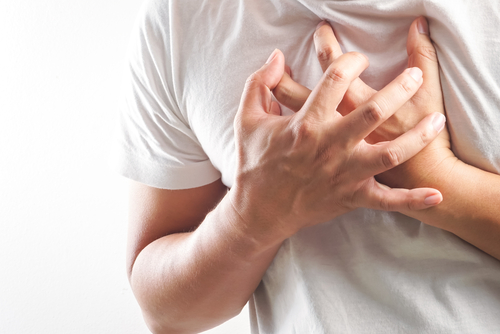 man clutching chest with both hands suffering from heart attack