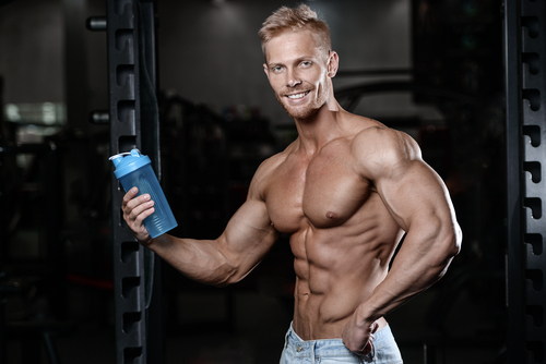 ripped guy holding sports bottle with protein powder supplement