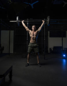 fit man doing overhead barbell lift