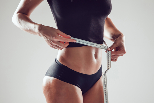 athletic woman measuring waist circumference