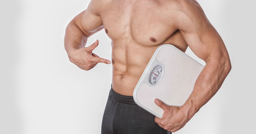 guy with 6 pack abs holding weighing scale