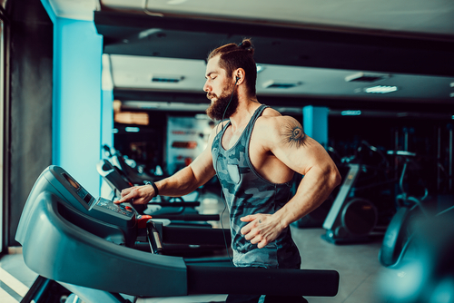 buff guy running on treadmill in gym