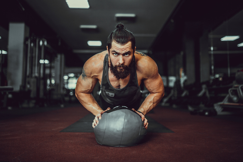 fit man doing planks with med ball
