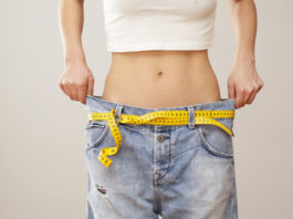 slim woman wearing oversize jeans showing weight loss