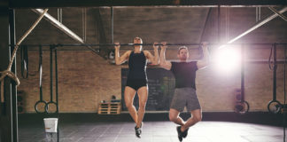 fit couple doing bar pull ups