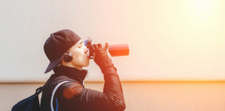 man drinking protein supplement from sports bottle