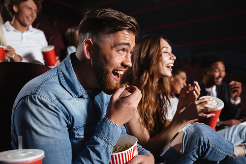 couple laughing while watching movie in theater with popcorn