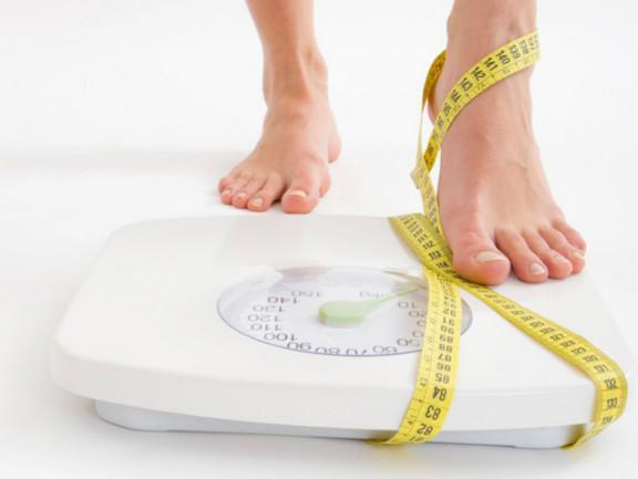 stepping on the scale with tape measure wrapped around foot