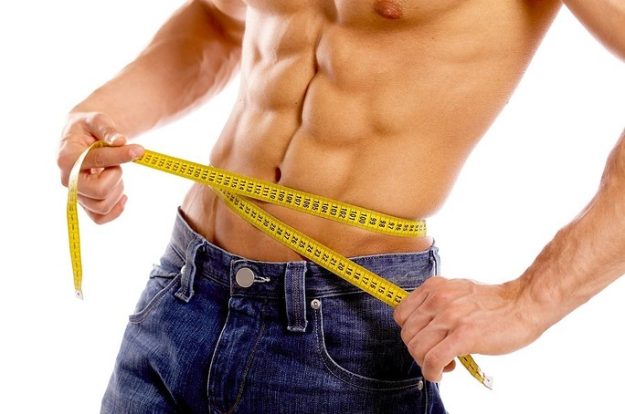 fit man with defined abs measuring with tape