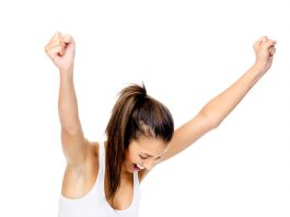 triumphant woman raise arms looking at scale, weight loss
