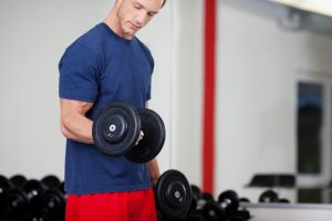 man with muscular arm lifting weights, dumb bell