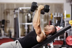 fit man doing dumbbell press on inclined bench in gym