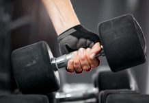 woman's hand with fitness gloves holding a dumb bell