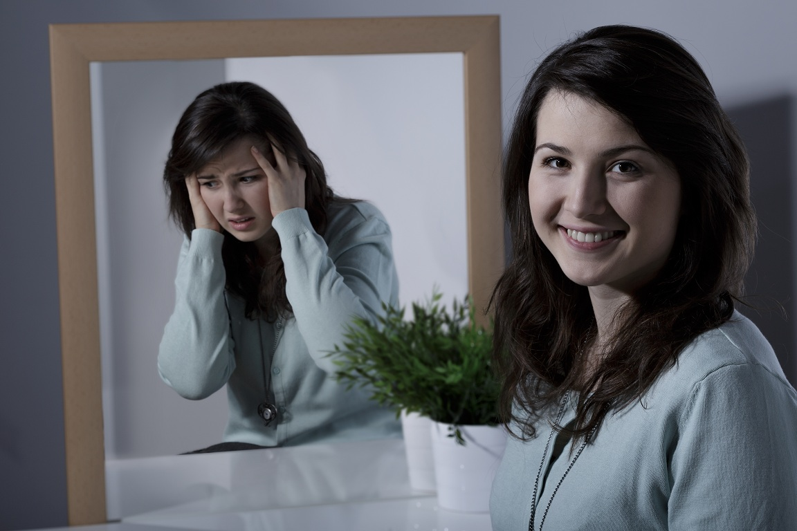 woman with bipolar image on mirror, split personality
