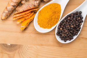 black pepper and turmeric in spoon
