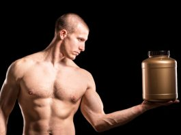 fit muscular man holding whey protein container