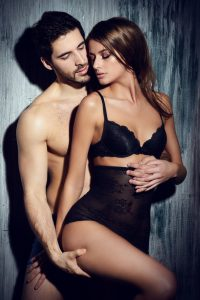 shirtless man holding thigh of woman in lingerie