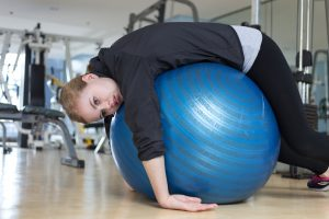 exhausted woman slumped over exercise stability ball