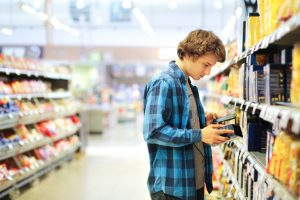 young man in grocery store looking at food label