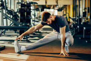 man stretching for warm up in gym workout
