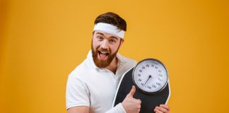 fitness buff holding scale and happy