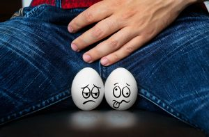 eggs with sick faces against man's crotch. testicular problem