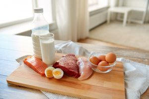 protein rich food on chopping board, egg, salmon, milk