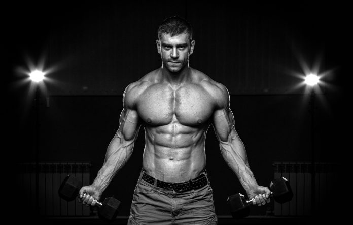 fit buff man holding dumbbells showing chest muscle