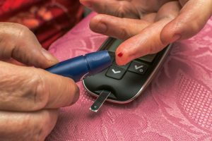 pricking finger to test blood sugar with glucometer