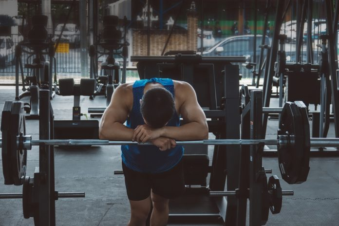 tired man slouched over barbell in gym after over training