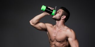 ripped man drinking from sports bottle
