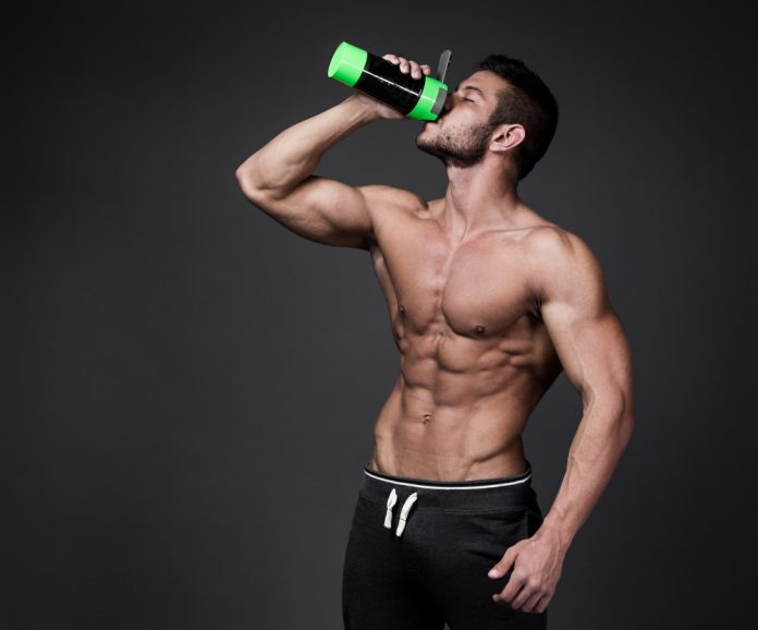 ripped man who takes Progentra drinking from sports bottle