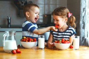 happy children eating strawberries with milk