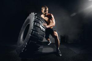 man lifting tire intense circuit exercise
