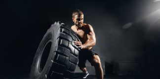 man lifting tire intense circuit exercise