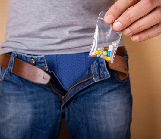 man holding various sexual enhancement pills including Progentra