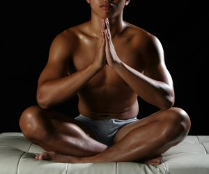 naked man meditating in bed