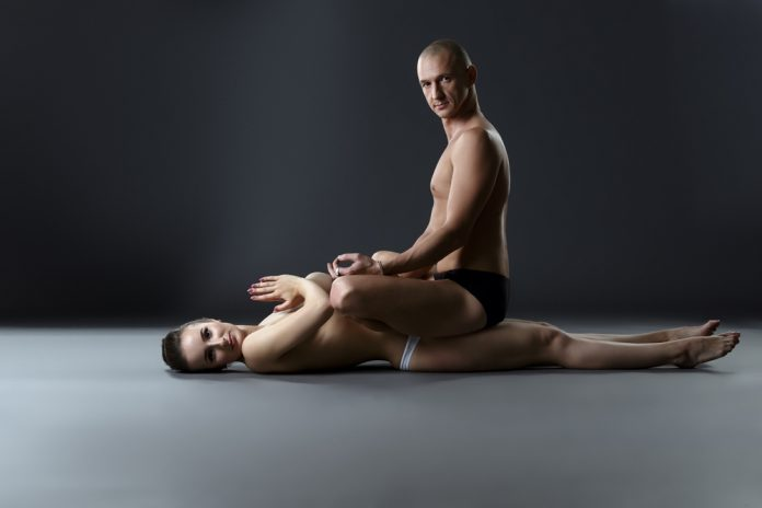 naked couple meditating and doing yoga together with man