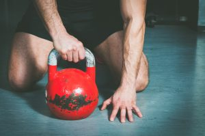 man lifting kettle bell stronger