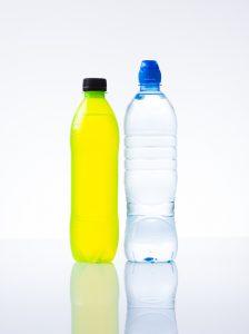 bottle of sports drink beside a bottle of water