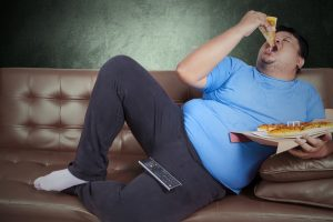 obese man eating pizza while seated on couch